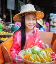33982756 - chikd sit on the boat and hold the fruit basket in traditional floating market , thailand.